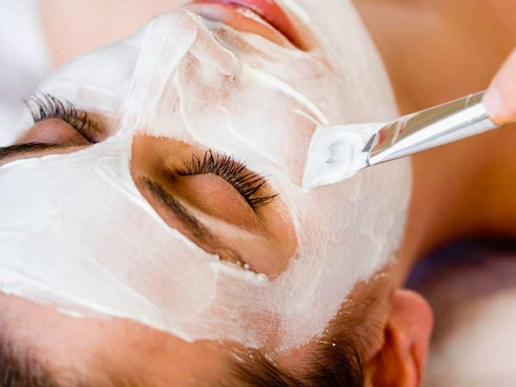 A women getting a facial mask applied at a health spa.