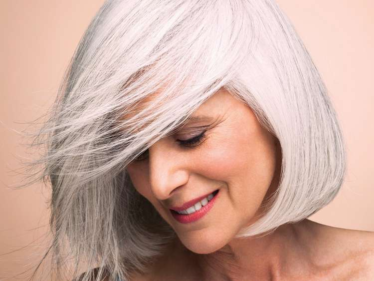 Woman with silvery, grey hair styled.