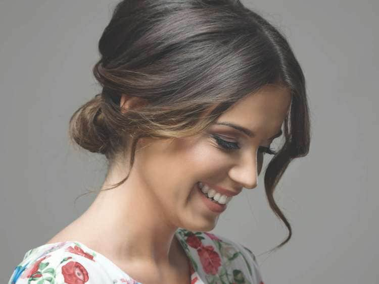 Woman with updo smiling.